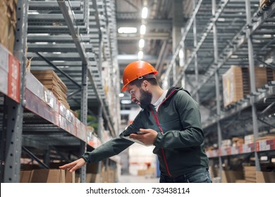 Warehouse manager checking his inventory in a large warehouse