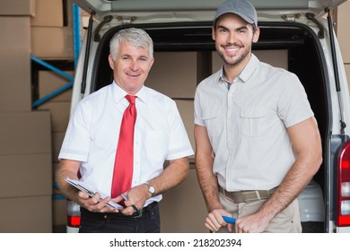 Warehouse manager and delivery driver smiling at camera in a large warehouse