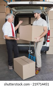 Warehouse manager and delivery driver talking beside van in a large warehouse