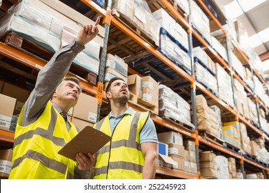 Warehouse manager and foreman working together in a large warehouse