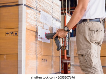 Warehouse manager holding barcode scanner with scanning on product pallet for deliver.