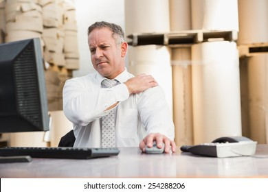Warehouse manager suffering from shoulder pain in a large warehouse