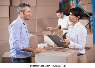Warehouse manager writing on clipboard talking to colleague in a large warehouse