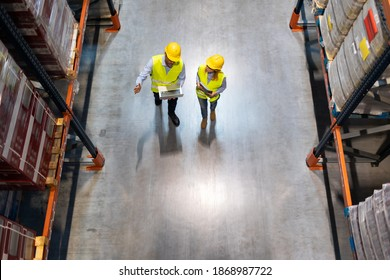 Warehouse managers consult plans using laptop, above view