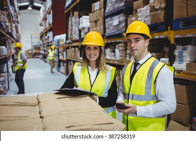 Warehouse managers looking at clipboard with helmets