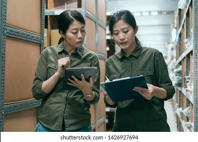 Warehouse managers looking at clipboard in warehouse. two female staffs coworkers talking and discussing while doing stocktaking in stockroom. group of woman workers working in storehouse together.