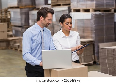 Warehouse managers working on laptop in a large warehouse