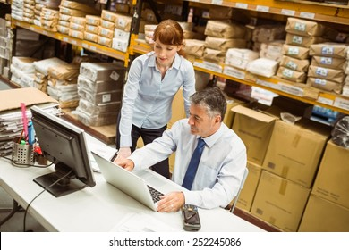 Warehouse managers working together on laptop in a large warehouse