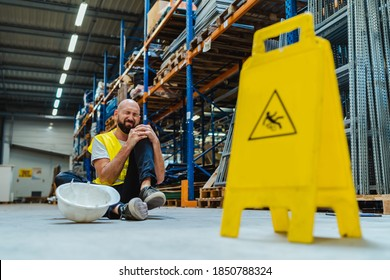 warehouse mployee holding his painful knee after falling on the slippery floor