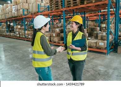 Warehouse operator teamwork. two female storehouse owner partners shaking hand. young asian woman in hard hats handshaking and smiling with great deal while standing in large stockroom together.