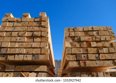 Warehouse for sawing boards on a sawmill outdoors. Timber mill, sawmill: storage of planed wooden boards. Piles of wooden boards in the sawmill, planking.