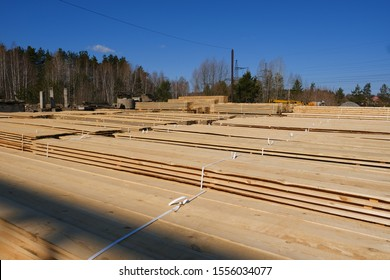 Warehouse for sawing boards on a sawmill outdoors. Timber mill, sawmill: storage of planed wooden boards