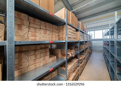 Warehouse shelves with cardboard boxes and packs in paper packaging.