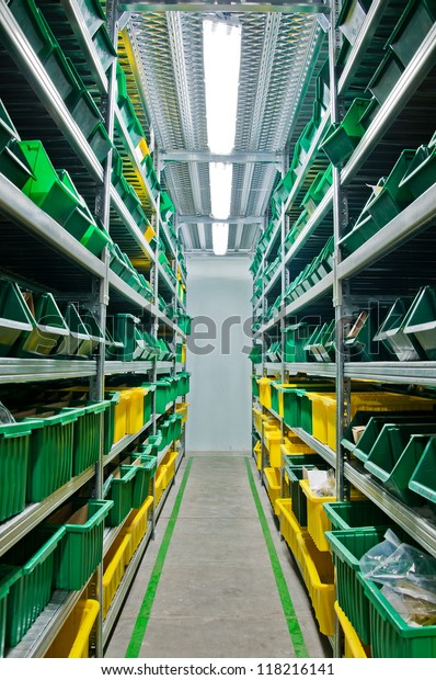 warehouse with steel shelves and green boxes