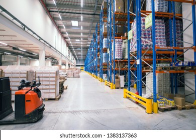 Warehouse storage facility interior. Large distribution center with shelves full of palette boxes and forklift machine.