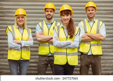 Warehouse team with arms crossed wearing hard hat in a large warehouse