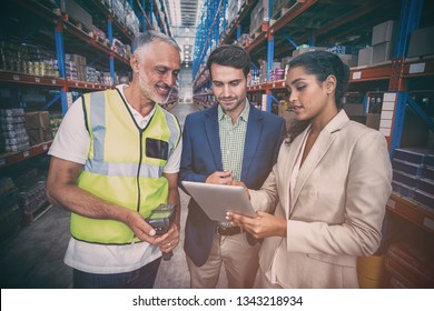 Warehouse team discussing with digital tablet in warehouse
