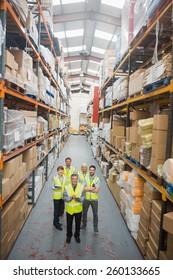 Warehouse team smiling at camera in warehouse