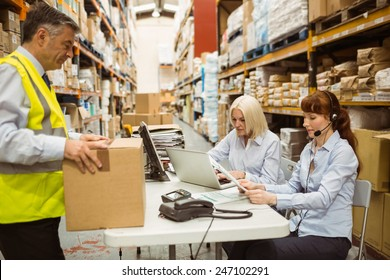 Warehouse team working together on shipment in a large warehouse