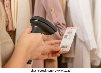 A warehouse woman employee accepts clothes using barcode scanner reading a bar code from price tag of female blazer and adds to the computer base.