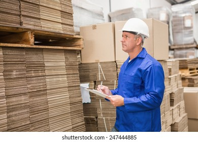 Warehouse worker checking his list on clipboard in a large warehouse