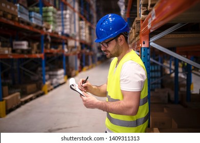 Warehouse worker checking inventory in large distribution center. Controlling goods storage and distribution.