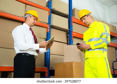 Warehouse Worker Checking The Inventory With Manager In A Large Warehouse