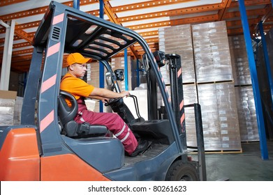 Warehouse worker distributing goods in a storehouse with forklift truck loader