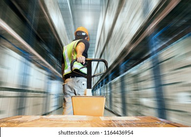 Warehouse worker dragging hand pallet truck or pallet jack with shipment product, motion blurred warehouse.