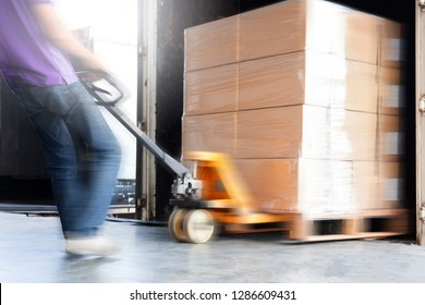 warehouse worker are dragging hand pallet truck or manual forklift with the shipment pallet unloading into a truck.