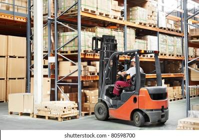 warehouse worker driver in uniform loading cardboard boxes by forklift stacker loader