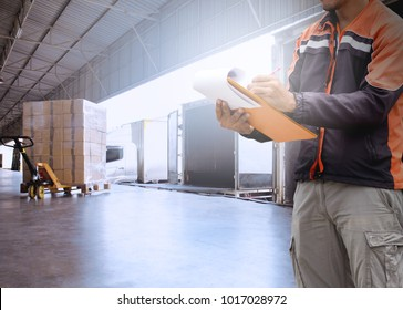 Warehouse worker hand holding clipboard with load control the shipment  into a truck.