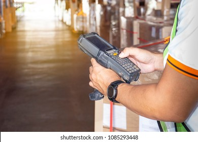 Warehouse worker holding bluetooth barcode scanner with inventory and checking a product in warehouse factory