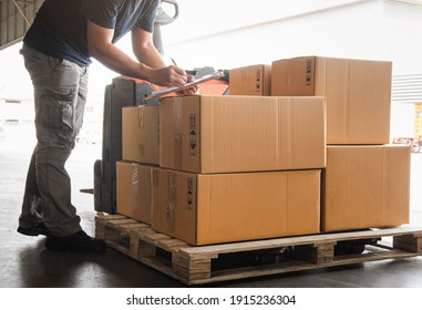 Warehouse worker holding clipboard his doing inventory management cargo boxes. Checking stock.  Shipment boxes. Warehousing storage.