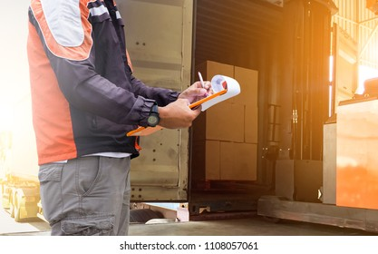 Warehouse worker holding clipboard with writing check list for loading pallet  into a truck.