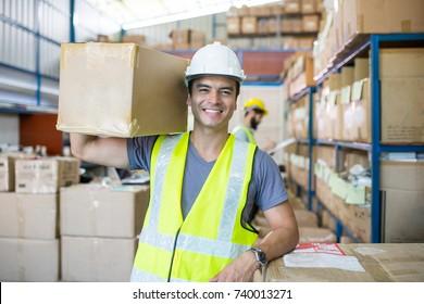 Empleado de almacén sostiene el paquete en el hombro para su entrega al cliente.