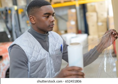 Warehouse worker holding roll of shrink wrap