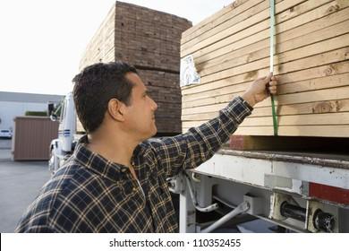 Warehouse worker loading wooden planks on truck carrier