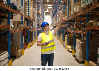 Warehouse worker in protective reflective uniform with hardhat checking inventory and counting product on shelf in large storage area.