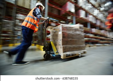 Warehouse worker pushing forklift at work