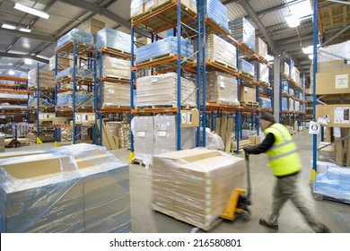 Warehouse worker pushing pallet truck with cardboard boxes