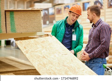 warehouse worker show the best variant of wooden board in their market, customer looking for building material