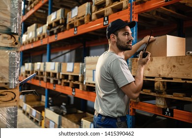 Warehouse worker talking over walkie-talkie while organizing package shipment for distribution.