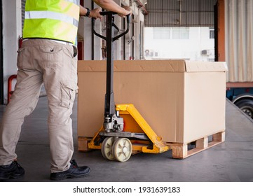 Warehouse worker unloading heavy shipment box pallet at the warehouse. work tools hand pallet truck. cargo shipping warehouse.