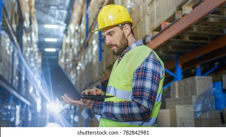 Warehouse Worker Uses Laptop. He's Standing in the Middle of  a Big Distribution Center with Big Storage Racks and Pallets on Them.