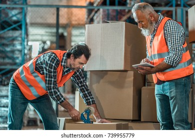 warehouse worker using digital tablet and looking at colleague packing box with adhesive tape