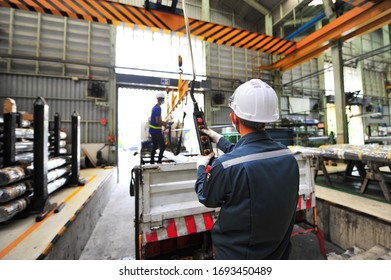 Warehouse worker wearing white safety helmet holding control remote and manipulating indoor overhead crane on factory pushing buttons on pendant control to lift up round steel bars onto the truck.