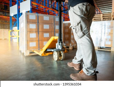 Warehouse worker is working with hand pallet truck or pallet jack and the shipment.