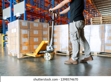 warehouse worker is working with hand pallet truck or pallet jack and shipments in distribution warehouse.