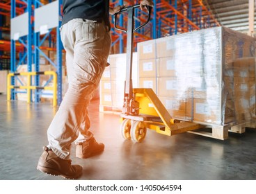 warehouse worker is working with hand pallet truck or pallet jack and cargo pallet.